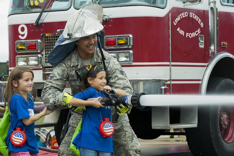 U.S. Air Force Senior Airman James Permito, 18th Civil Engineer Squadron firefighter, holds the water hose steady as children shoot at cones during Skoshi Warrior Nov. 14, 2015, at Kadena Air Base, Japan. Skoshi Warrior is an annual event for military children and provides a fun environment for children to experience the deployment process their parents go through when tasked to deploy. (U.S. Air Force photo by Airman 1st Class Corey M. Pettis/Released)