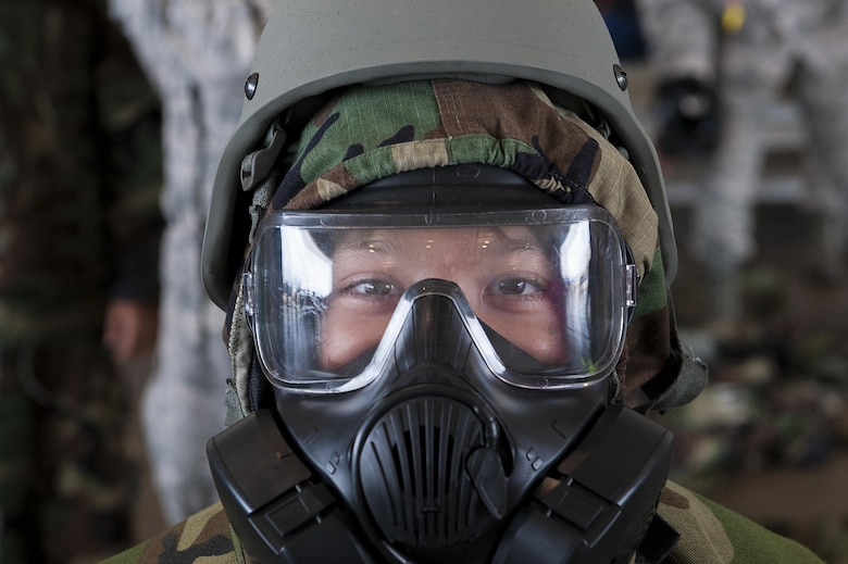 A child tries on a gas mask and mission oriented protective posture (MOPP) gear at Skoshi Warrior Nov. 14, 2015, at Kadena Air Base, Japan. Skoshi Warrior is an annual event designed to help children understand some of the deplyment processes that their military parents go through. (U.S. Air Force photo by Airman 1st Class Corey M. Pettis/Released)
