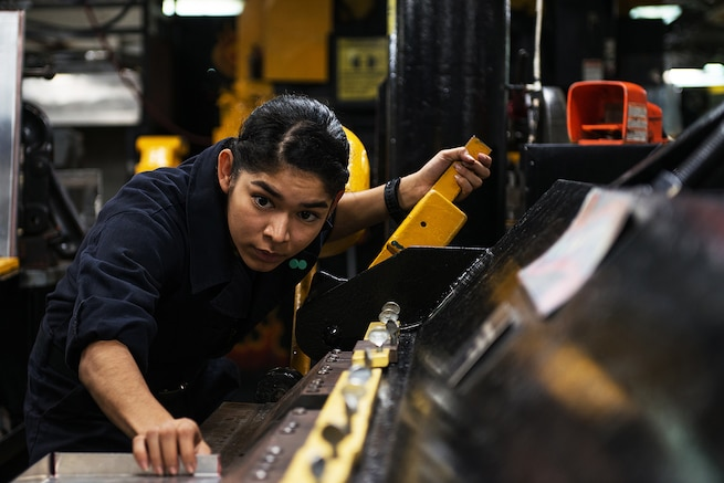 U.S. Navy Seaman Margarita Melgoza bends sheet metal aboard the USS Ronald Reagan in waters south of Japan, Nov. 19, 2015. U.S. Navy photo by Petty Officer 3rd Class James Lee