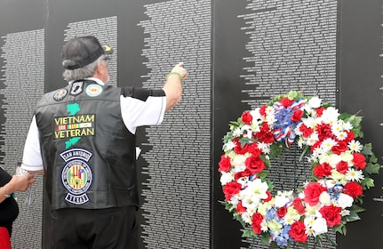 "A Vietnam War veteran recognizes a name on the American Veteran Traveling Wall during the ""Salute To Veterans"" event at MacArthur Field on Fort Sam Houston Friday. Special recognition was given to those who fought during the Vietnam War. The backdrop presented during the ceremony is an 80 percent replica of the Vietnam Memorial Wall that travels through the country to commemorate those who fell during the Vietnam War. Although special recognition was given to Vietnam Veterans during the ceremony, all veterans were recognized and thanked for all they have given to the country with pride and honor."