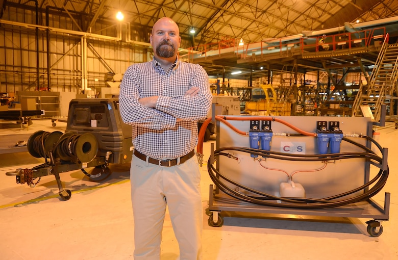 Retired Master Sgt. Michael Childers, the 436th Maintenance Squadron production supervisor, poses inside the isochronal maintenance hangar at Dover Air Force Base, Del. The MC-7 high-volume, low-pressure air cart is shown on the left while the filtration system Childers created is shown on the right. (U.S. Air Force photo/Greg L. Davis)