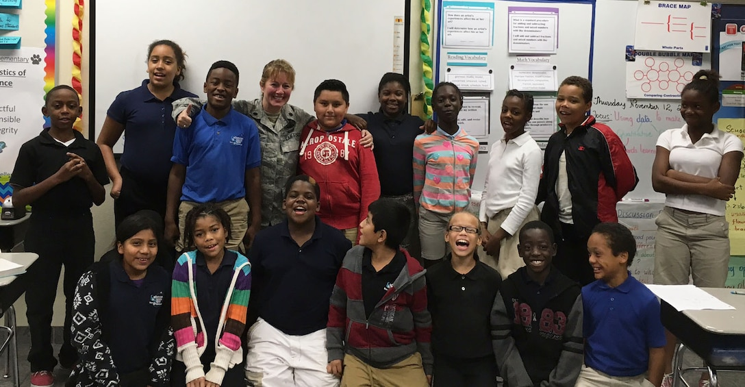 Students from Ms. Michelle Agard's 4th grade class at Endeavour Elementary Magnet School in Cocoa, Fla., pose with retired Lt. Col. Susan A. Romano Nov. 12, 2015.  The students paid tribute to local servicemembers for Veterans Day and invited Romano, the class' reading and writing mentor, to be a part of the festivities.  (Courtesy photo)