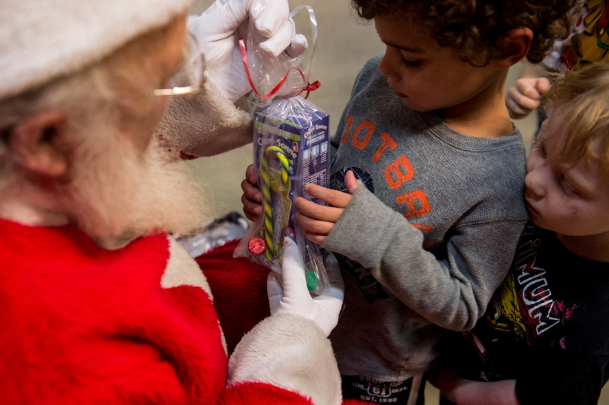 A child receives a gift from Santa Claus during the Deployed Family Member Thanksgiving dinner inside Fire Station 1 at Spangdahlem Air Base, Germany, Nov. 18, 2015. As one of the attractions for kids Santa Claus handed out gifts and received Christmas present requests. (U.S. Air Force photo by Senior Airman Rusty Frank/Released)