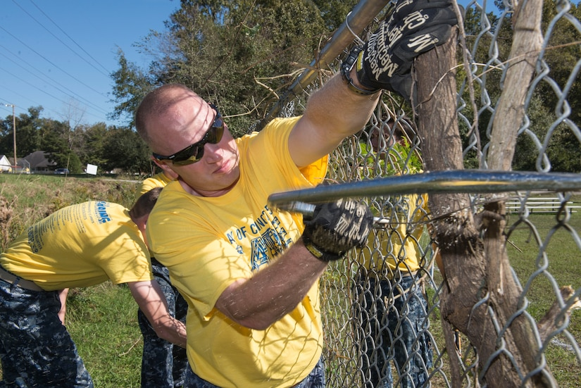 Senior Chief Petty Officer Justin Thompson, an instructor at the Navy Nuclear Power Training Command at Joint Base Charleston – NWS, S.C., helps remove an in-grown tree from the fence at the Young Men's Christian Association in Summerville, S.C., on Nov. 13, 2015. Thompson and other JB Charleston members were at the YMCA and several other locations to participate in the Day of Caring event. (U.S. Air Force photo/Airman 1st Class Thomas T. Charlton)