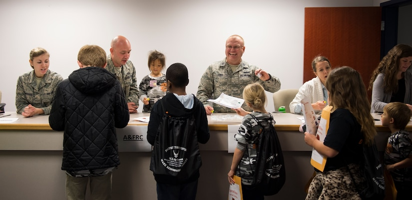 Joint Base Charleston members and volunteers simulate a deployment line with children participating in a mock deployment line event November 14, 2015, at the 628th Logistics Readiness Squadron on JB Charleston – Air Base, S.C. The event was held to give children a glimpse into what it's like for their parents to prepare for a deployment. During the event, children transitioned through a mock processing line where they spoke to several base agencies including the chapel, medical, finance, Airman and Family Readiness Center, base leadership and more. (U.S. Air Force photo/Airman 1st Class Clayton Cupit)