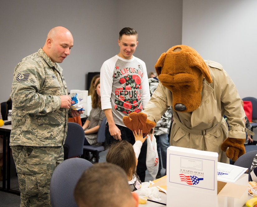 McGruff the crime dog high fives with children participating in a mock deployment line event November 14, 2015, in a classroom at the 628th Logistics Readiness Squadron on JB Charleston – Air Base, S.C. The event was held to give children a glimpse into what it's like for their parents to prepare for a deployment. During the event, children transitioned through a mock processing line where they spoke to several base agencies including the chapel, medical, finance, Airman and Family Readiness Center, base leadership and more. (U.S. Air Force photo/Airman 1st Class Clayton Cupit)