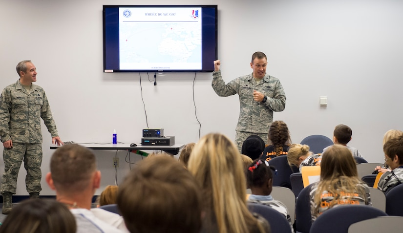 Col. John Lamontagne, 437th Airlift Wing commander, talks about a deployment scenario with children during a mock deployment line event November 14, 2015, at the 628th Logistics Readiness Squadron on JB Charleston – Air Base, S.C. The event was held to give children a glimpse into what it's like for their parents to prepare for a deployment. During the event, children transitioned through a mock processing line where they spoke to several base agencies including the chapel, medical, finance, Airman and Family Readiness Center, base leadership and more. (U.S. Air Force photo/Airman 1st Class Clayton Cupit)
