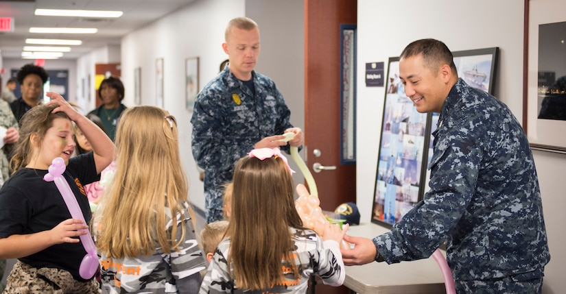 Sailors from Joint Base Charleston interact with children participating in a mock deployment line event by crafting balloon animals for them November 14, 2015, at the 628th Logistics Readiness Squadron on JB Charleston – Air Base, S.C. The event was held to give children a glimpse into what it's like for their parents to prepare for a deployment. The children transitioned through a mock processing line where they spoke to several base agencies including the chapel, medical, finance, Airman and Family Readiness Center, base leadership and more. (U.S. Air Force photo/Airman 1st Class Clayton Cupit)