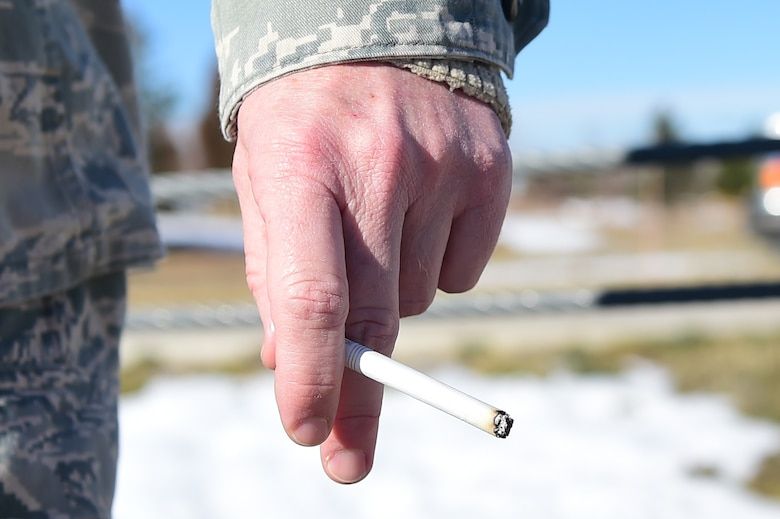 An Airman smokes a cigarette in a designated area Nov. 19, 2015, at Buckley Air Force Base, Colo.  The Great American Smokeout is held every year in November and is an initiative by the American Cancer Society to get people to stop smoking. According to the American Cancer Society, the day is set aside to encourage smokers to go the distance, and finally give up smoking. (U.S. Air Force photo by Airman 1st Class Luke W. Nowakowski/Released)