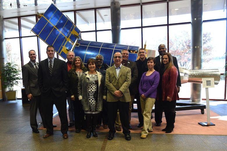 Aurora Defense Council members stand in front of a Defense Support Program spacecraft model in the 460th Operations Group Mission Control Station Nov. 19, 2015, on Buckley Air Force Base, Colo. The council members had a chance to tour the MCS lobby and get an inside look at a radome as part of a tour after the 460th Space Wing hosted the Aurora Defense Council meeting. (U.S. Air Force photo by Airman 1st Class Samantha Meadors/Released)