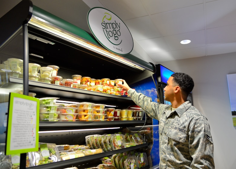 Airman 1st Class Jorge Rijo, 436th Aerospace Medicine Squadron bioenvironmental engineer, grabs a to-go fruit cup during the soft opening of the Patterson Dining Facility Nov. 17, 2015, at Dover Air Force Base, Del. The dining facility now offers grab-n-go items outside of normal operating hours. (U.S. Air Force photo/Senior Airman William Johnson)