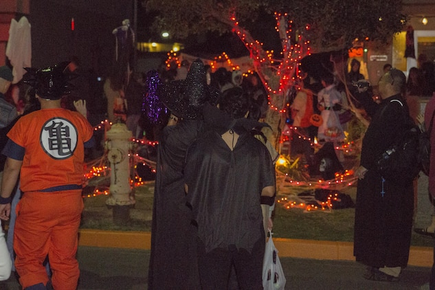 Station volunteers and orphans from Garden of Light Children's Home in Hatsukaichi, Hiroshima Prefecture, Japan, trick-or-treat during a Halloween event at Marine Corps Air Station Iwakuni, Oct. 31, 2015. During their visit, 50 station volunteers escorted 15 orphans to a haunted house operated by Marines from Marine Wing Support Squadron 171, enjoyed bonding over dinner and trick-or-treating around the air station. While trick-or-treating, visitors and volunteers could see how station residents celebrate the spooky holiday, from the eccentric costumes to the decorated houses.