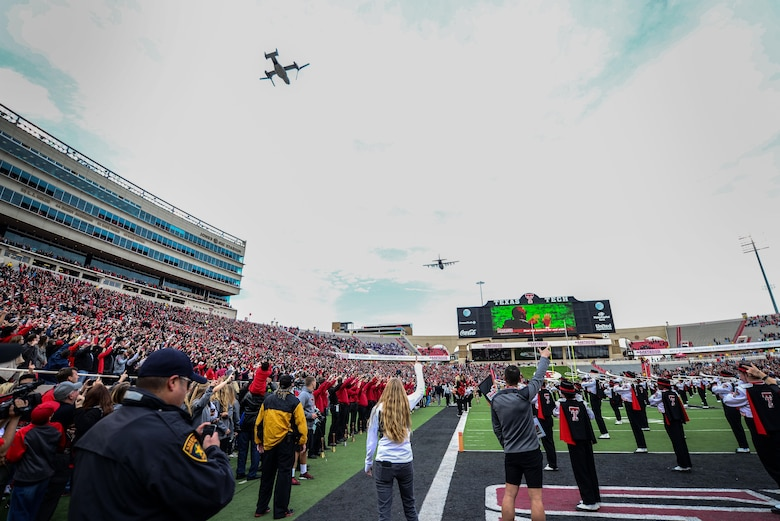 "An MC-130J Commando II and CV-22 Osprey fly over Jones AT&T Stadium as Texas Tech fans play and sing ""The Matador Song"" Nov. 14, 2015, in Lubbock, Texas. The flyover kicked off Tech's ""Celebrating America"" appreciation game marking the school's gratitude and respect for military and first responders. (U.S. Air Force photo/Airman 1st Class Shelby Kay-Fantozzi)"