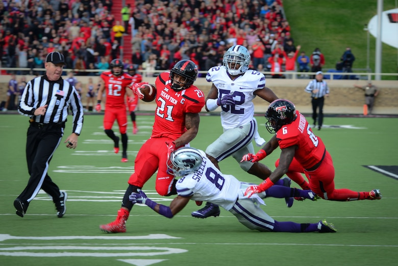 "Texas Tech running back Deandre Washington breaks through an attempted tackle by Kansas State University defensive back Duke Shelley and linebacker Charmeachealle Moore to run an 80-yard touchdown Nov. 14, 2015, in Lubbock, Texas. The TTU home game against Kansas State was their ""Celebrating America"" appreciation game, marking the school's gratitude and respect for military and first responders. (U.S. Air Force photo/Airman 1st Class Shelby Kay-Fantozzi)"