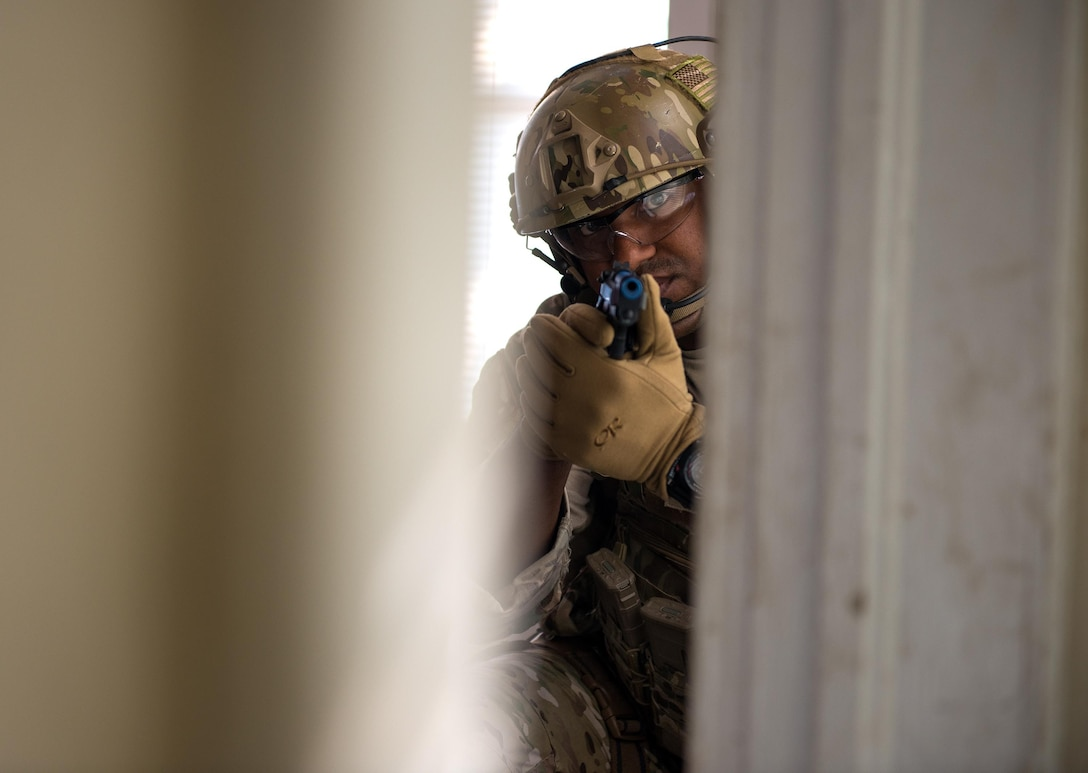 A tactical air control party Airman aims a weapon through a doorway while clearing a structure during special weapons and tactics school at Southern Nazarene University in Bethany, Okla. The class was instructed by the Oklahoma County Sheriff's Office Oct. 26 to Nov. 6, 2015. The Airman is assigned to the 146th Air Support Operations Squadron from the Will Rogers Air National Guard Base in Oklahoma City. (U.S. Air National Guard photo/Master Sgt. Andrew M. LaMoreaux)
