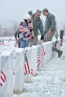 Chief Master Sgt. Carmelo Vega Martinez and his daughter Frances place flags beside headstones at the Utah Veterans Memorial Cemetery and Memorial Park in Bluffdale, Utah, Nov. 10, 2015. More than 100 Airmen from Hill Air Force Base placed 5,646 flags in honor of veterans and their families. (U.S. Air Force photo/R. Nial Bradshaw)