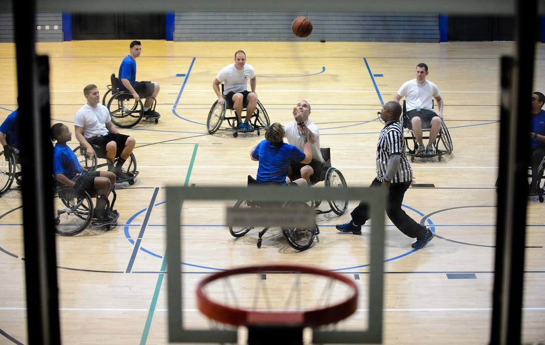 Members of the 10th Expeditionary Airlift Evacuation Flight and 721st Aircraft Maintenance Squadron tip off during a Wounded Warrior Basketball game Nov. 13, 2015, at Ramstein Air Base, Germany. The Warrior Transition Battalion hosted the tournament to show Airmen how wounded service members stay resilient through their recovery. (U.S. Air Force photo/Staff Sgt. Armando A. Schwier-Morales)