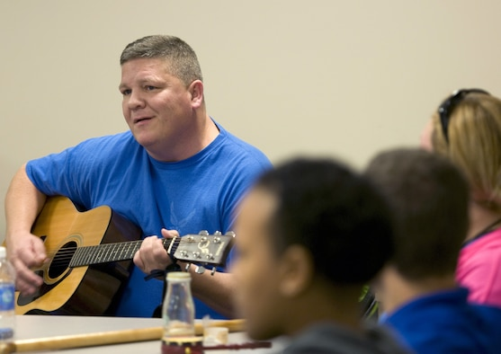 Former Maj. Frank Vassar plays one of his songs to fellow wounded Airmen during a music therapy session Nov. 19, 2015, on Joint Base Andrews, Md., as part of Warrior Care Month. Airmen had the chance to use a variety of musical instruments and collaborate on songs in the sessions, which were intended to show wounded warriors a unique approach to therapy. (U.S. Air Force photo/Sean Kimmons)