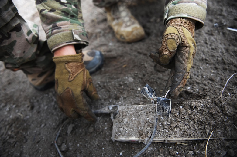 An Airman with the 775th Explosive Ordnance Disposal Flight examines wiring on a pressure plate used in an improvised explosive device during a training event at Hill Air Force Base, Utah, the training took place from Nov. 2-6, 2015.  Being an EOD technician requires Airmen to be adept in math, chemistry, forensics, mechanics, advanced electrical circuits and have the ability to put the knowledge to use under extreme pressure. (U.S. Air Force photo/Micah Garbarino)