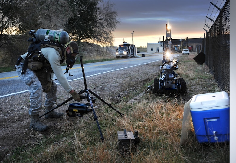 With the aid of lights and cameras on a remote-controlled robot, Senior Airman Garret Corbett, an explosive ordnance disposal technician with the 775th EOD Flight at Hill Air Force Base, sets up a mobile to examine the contents of a cooler during a training scenario on investigating suspicious packages. Once Corbett takes the X-ray, he can process them in a mobile computer lab in the command truck. (U.S. Air Force photo/Micah Garbarino)
