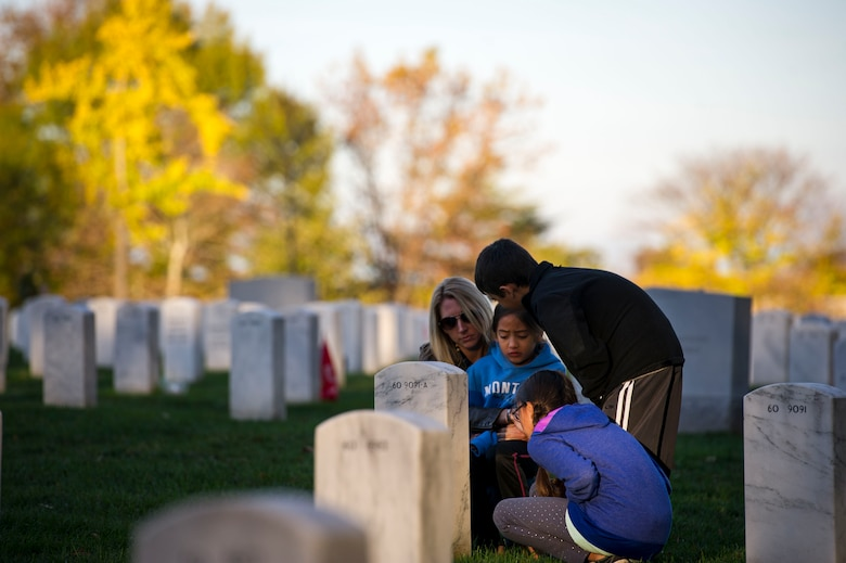 Heather Gray and her three children Ava (left), Garrett (middle) and Nyah visit Maj. David Gray at Arlington National Cemetery, Va., Nov. 11, 2015. David, a husband and father to the three children, was killed in action Aug. 8, 2012, during a deployment to Afghanistan. Heather and her children moved from Colorado, where David was stationed at Fort Carson, earlier this year for the first time since his death. (U.S. Air Force photo/Staff Sgt. Christopher Gross)