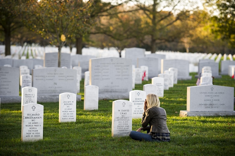 Heather Gray sits in front of the headstone for her husband, Maj. David Gray, at Arlington National Cemetery, Va., Nov. 11, 2015. Her husband was killed in action Aug. 8, 2012, during a deployment to Afghanistan. Heather and her three children moved from Colorado, where David was stationed at Fort Carson, earlier this year for the first time since his death. (U.S. Air Force photo/Staff Sgt. Christopher Gross)