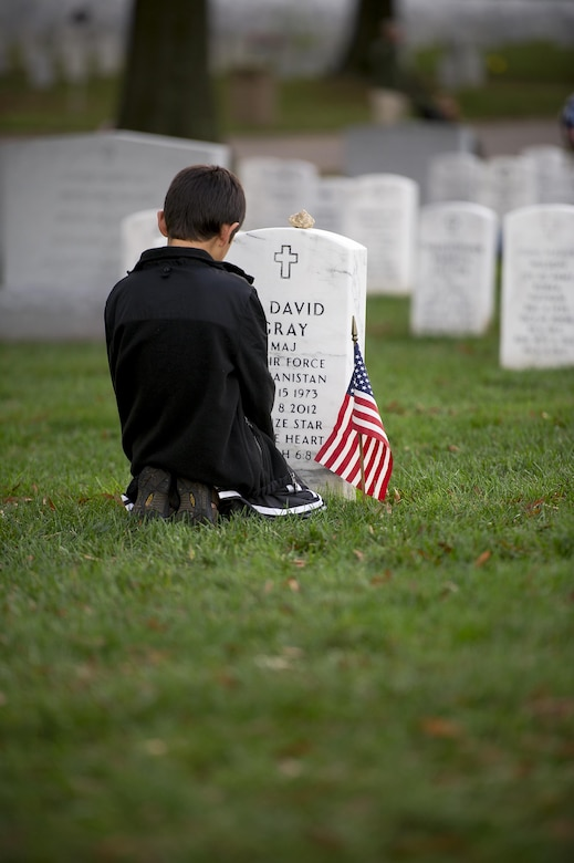 Garrett Gray, 9, kneels in front of the headstone for his father, Maj. David Gray, at Arlington National Cemetery, Va., Nov. 11, 2015. His father was killed in action Aug. 8, 2012, during a deployment to Afghanistan. David's wife, Heather, and her three children moved from Colorado, where David was stationed at Fort Carson, earlier this year for the first time since his death. (U.S. Air Force photo/Staff Sgt. Christopher Gross)