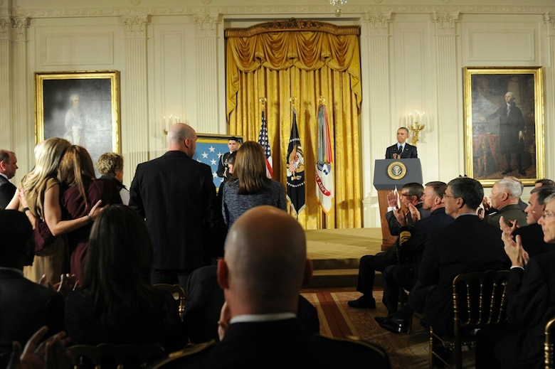 Heather Gray (far left) stands up with other Gold Star wives, as they are recognized by President Barack Obama during a Medal of Honor presentation for retired Army Capt. Florent Groberg at the White House Nov. 12, 2015. Groberg was with Heather's husband, Maj. David Gray, when he was killed in action Aug. 8, 2012, during a deployment to Afghanistan. (Courtesy photo)