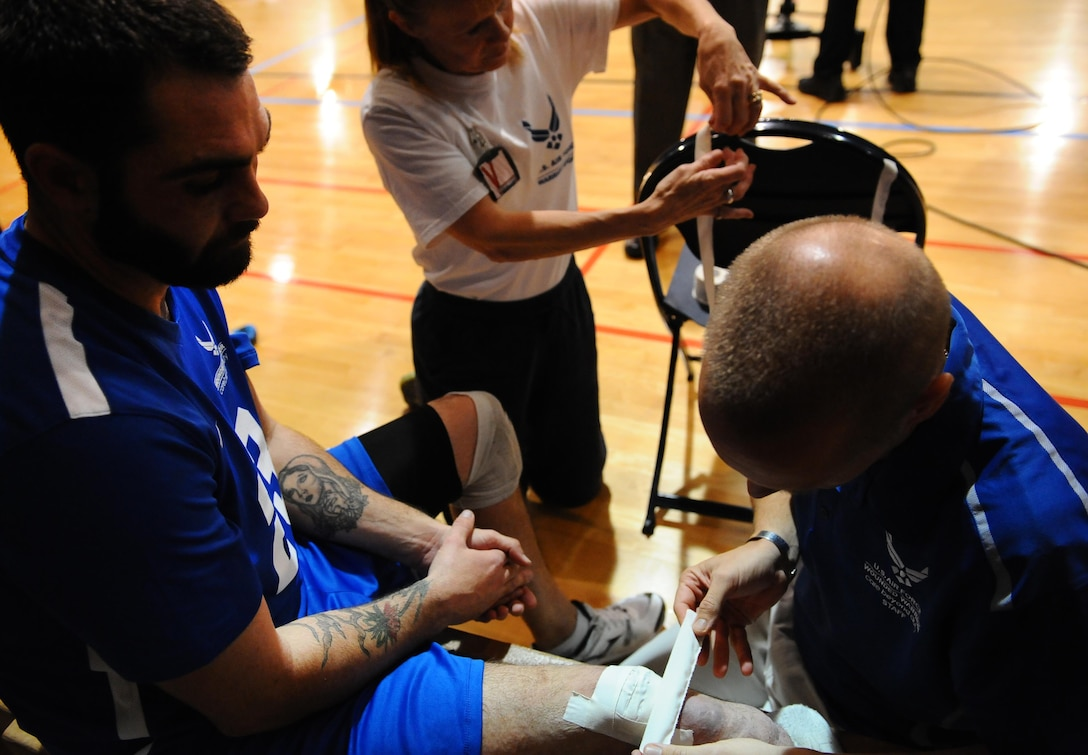 Retired Staff Sgt. Nicholas Dadgostar gets his leg taped after the Warrior Care Month Sitting Volleyball Tournament championship game at the Pentagon in Washington, D.C., Nov. 19, 2015. The Air Force won the tournament by beating the Marines. (U.S. Air Force photo/Senior Airman Hailey Haux)