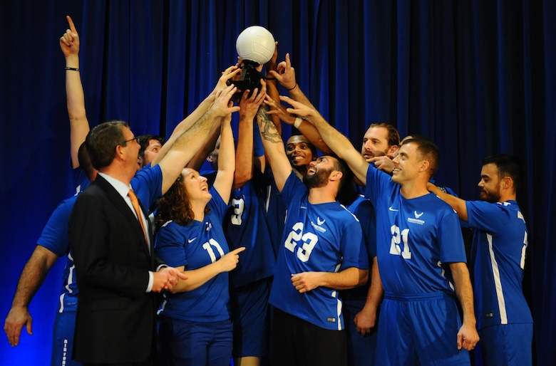 The Air Force Wounded Warrior Team, along with Defense Secretary Ash Carter, raise the coveted 1st place trophy after winning the Warrior Care Month Sitting Volleyball Tournament at the Pentagon in Washington, D.C., Nov. 19, 2015. The Air Force team edged out the Marines in the final match. (U.S. Air Force photo/Senior Airman Hailey Haux)