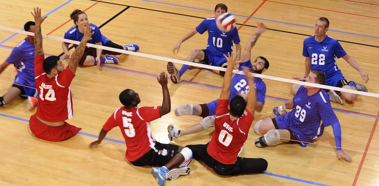 A member of the Air Force wounded warrior volleyball team spikes the ball during a volleyball match as part of the Warrior Care Month Sitting Volleyball Tournament at the Pentagon in Washington, D.C., Nov. 19, 2015. The Air Force Wounded Warrior Team won the match against the Marines, and went on to take home the trophy for the tournament. (U.S. Air Force photo/Staff Sgt. Whitney Stanfield)