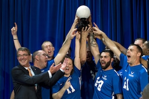 Defense Secretary Ash Carter awards a trophy to the Air Force sitting volleyball team for winning a joint service sitting volleyball tournament at the Pentagon, Nov. 19, 2015. DoD photo by EJ Hersom
