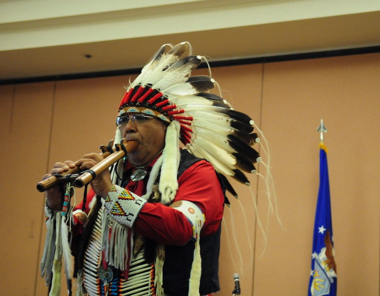 """Lucky Preston plays a drone flute during an American Indian Heritage Month event Nov. 19, 2015, at Beale Air Force Base, California. The drone flute is a unique instrument because one side plays the melody of the song, while the other side holds a """"drone"""" note. (U.S. Air Force photo by Staff Sgt. Zachary Vucic)"""