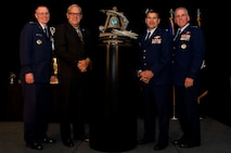 (L-R) Maj. Gen. Kenneth D. Lewis, Jr., director, Air, Space and Information Operations, Air Force Reserve Command, Robins Air Force Base, Georgia; Roger Rupp, Boeing Company and chair, Greater Riverside Chambers of Commerce Military Affairs Committee, Riverside, California; Col. Albert Lupenski, commander, 439th Airlift Wing, Westover Air Reserve Base, Massachusetts; and Maj. Gen. John C. Flournoy, Jr., commander Fourth Air Force, gather at the 16th Annual Raincross Trophy Dinner Nov. 19, 2015, to present the Raincross Trophy, signifying the best wing in the numbered Air Force, to the 439 AW. The trophy, pictured here, bears the winning wing's name each year and remains at 4 AF headquarters. The annual winner receives a smaller replica for his or her wing to keep and display. (U.S. Air Force photo/Senior Master Sgt. Keith Baxter)