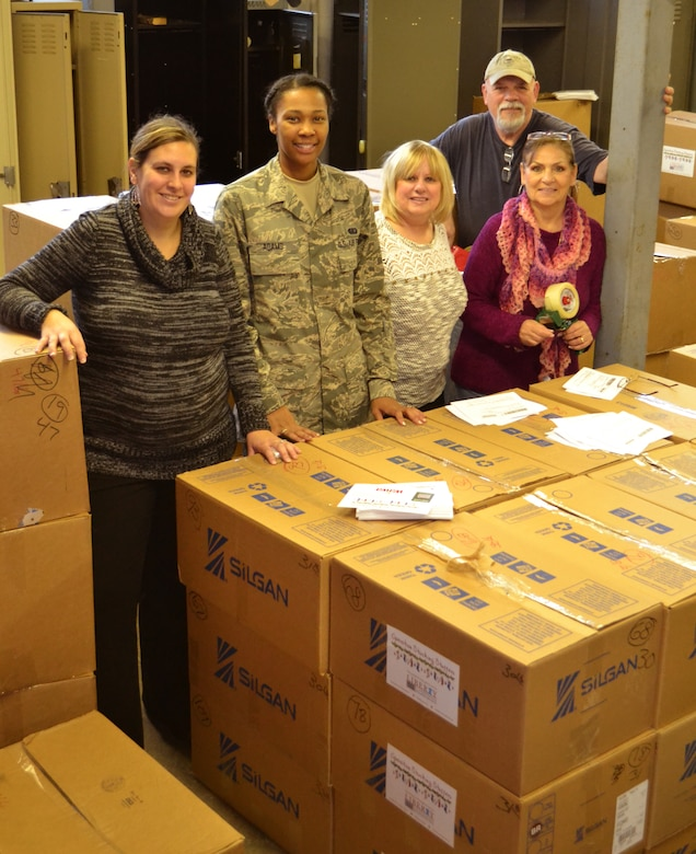 Members of the 111th Attack Wing, Liberty USO and volunteers stop working to take a photo with care packages they were preparing to send out at Horsham Air Guard Station, Pennslvania, Nov. 19, 2015. An estimated 5,000 package will be sent to deployed service members. (U.S. AIr National Guard photo by Tech. Sgt. Andria Allmond/Released)