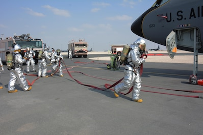 379th Civil Engineer Squadron firefighters work together to man several different fire hoses in an attempt to put out a simulated fire on a KC-135 Stratotanker and rescue an injured air crew member during a training exercise at Al Udeid Air Base, Qatar Nov. 20. Within minutes, several firefighters climbed on to the plane's left wing, entered the aircraft and pulled the injured air crew member to safety. Training exercises help first responders maintain their skillsets. (U.S. Air Force photo by Tech. Sgt. James Hodgman/Released)