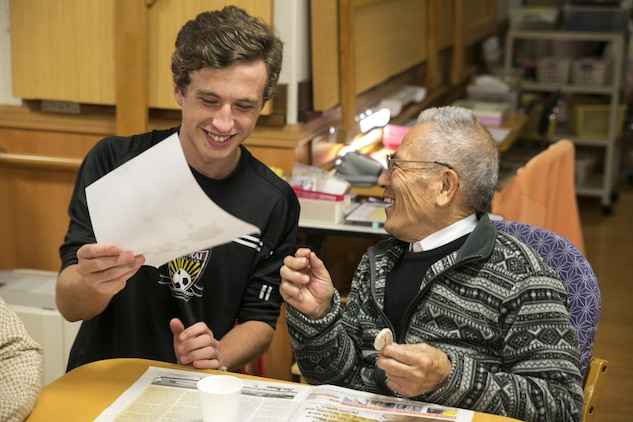 Aidan Lewis, a National Honor Society student at Marine Corps Air Station Iwakuni, Japan, helps Muranaka Masumi, a resident at the Kaede Nursing Home, paint a Christmas tree ornament during the students' visit to the home, Nov. 17, 2015. Giving back to the community during events like this helps strengthen the bond between the station and the local community.