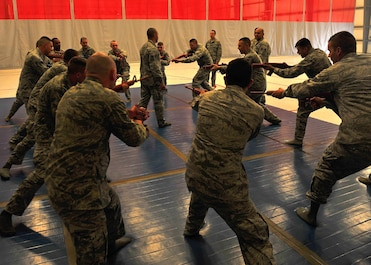 Combatives instructor from the 380th Expeditionary Security Forces Squadron train personnel on weapons control with firearms here, Oct. 15, 2015.  Techniques included learning basic unarmed strikes, weapon control and various body positions from the standing, kneeling and prone.  (U.S. Air Force photo/Staff Sgt. Kentavist Brackin)