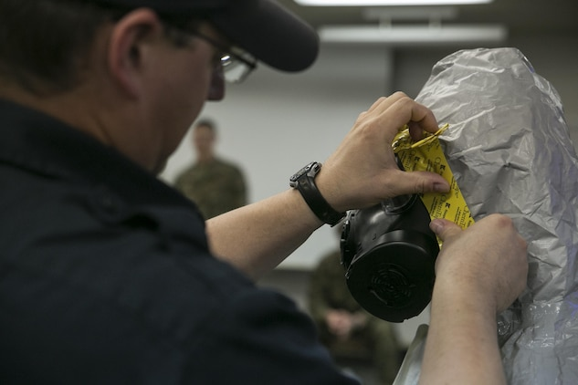 Bob Opett, a Hazardous Material Awareness and Operations course instructor, shows service members and firefighters how to properly seal the HazMat suit during the course at Marine Corps Air Station Iwakuni, Japan, Nov. 18, 2015. Provided by Bucks County Community College Department of Public Safety from Doylestown, Penn., the course is used to make individuals more aware of potential hazards and teach them initial response procedures.