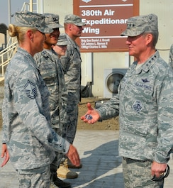 Gen. Hawk Carlisle, commander for Air Combatant Command, presents a commander's coin to Senior Master Sgt. Sarah, Wing Staff Agency superintendent for the 380th Air Expeditionary Wing during a visit to an undisclosed location in Southwest Asia, Oct. 19, 2015. Carlisle's visit was part of an annual tour of the Air Force Central Command area of responsibility to familiarize himself with Department of the Air Force assets.  (U.S. Air Force photo by Staff Sgt. Kentavist Brackin/Released)