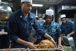 Culinary Specialist 1st Class John Mobley, from Philadelphia, prepares a turkey for carving for a Thanksgiving meal aboard the guided-missile destroyer USS Cole (DDG 67). Cole is conducting naval operations in the U.S. 6th Fleet area of responsibility in support of U.S. national security interests in Europe.