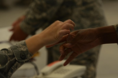 U.S. Air Force lodging personnel hands to inbound Airmen their room key in Southwest Asia Oct. 19, 2015. Lodging conducts a wide spectrum of tasks such as maintain-ing accountability of all housing facilities, including those of our sister services, and all laundry and latrine facilities. (U. S. Air Force photo by Tech. Sgt. Frank Miller/Released)