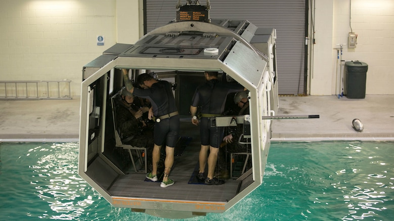 Marines with 2nd Low Altitude Air Defense Battalion and instructors with the Water Survival Training Facility prepare to be submerged in a pool while aboard a modular amphibious egress mock helicopter during training at Marine Corps Base Camp Lejeune, N.C., Nov. 18, 2015. The Marines participated in the training, which is designed to be a lifesaving course that provides service members with skills and the confidence to successfully and safely exit a helicopter that is submerged in a body of water.