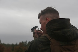 A Marine with 3rd Battalion, 6th Marine Regiment, looks a through compass during a 60mm mortar live-fire range at Marine Corps Base Camp Lejeune, N.C., Nov. 19, 2015. Despite heavy rainfall and wind, the Marines completed the mortar shoot in order to retain and refine their skills with the weapons system and prove they could complete a fire mission under any conditions.