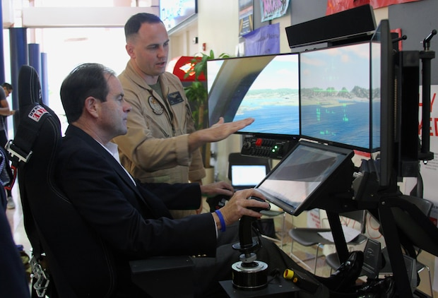 U.S. Marine Corps Capt. Richard O'Brien, center, the Eastern Recruiting Region aviation assistant for officer procurement, instructs Dr. John Broderick, the president of Old Dominion University, in piloting an F-35B Lightning II Joint Strike Fighter simulator at the university, Oct. 29. The simulators, part of the Marine Corps Flight Orientation Program, are used to generate interest among potential officer candidates for Marine aviation programs, and give the participants an idea of what flying the Corps' latest fighter jet is like.