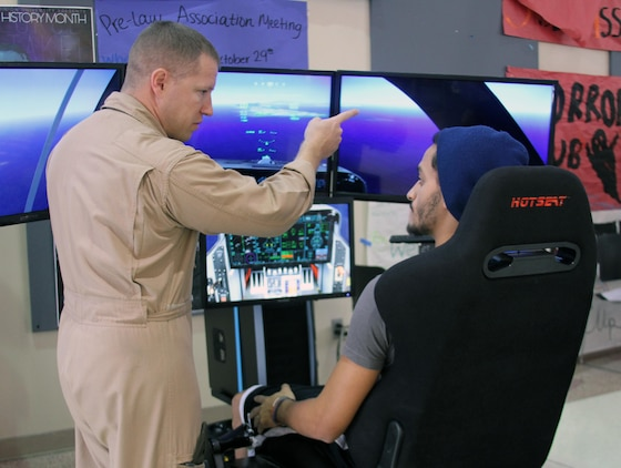 U.S. Marine Corps Capt. Richard Jacobs, the 4th Marine Corps District aviation assistant for officer procurement, instructs a student on flying the F-35B Lightning II Joint Strike Fighter simulator at Old Dominion University, Oct. 29. The simulators, part of the Marine Corps Flight Orientation Program, are used to generate interest among potential officer candidates for Marine aviation programs, and give the participants an idea of what flying the Corps' latest fighter jet is like.