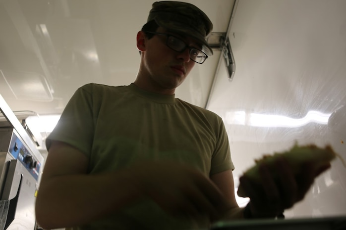 U.S. Army Spc. Dustin Freeman, a food services specialist with Headquarter and Headquarters Company, Special Troops Battalion, Sustainment Brigade, 1st Infantry Division, prepares a meal at evening chow for services members at Al Taqaddum Air Base, Iraq, Nov. 7, 2015. The food service members will continue to wake before the sun and toil into the late hours of the night to continue to provide support to U.S. and coalition forces in their day-to-day operations in support of Combined Joint Task Force-Operation Inherent Resolve.  (U.S. Marine Corps photo by Sgt. Owen Kimbrel)