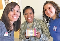 Cpl. Jonnie Farr, 601st Aviation Support Battalion, 1st Combat Aviation Brigade, 1st Infantry Division, received a cupcake during her birthday month from Ashlee Mastin, USO volunteer and Misty Vinduska from MeriTrust, the program sponsor.
