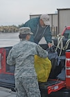 Fred Siebe, manager of the Douthit Gunnery Complex at Fort Riley, helps a Soldier from 299th Brigade Support Battalion, 2nd Armored Brigade Combat Team, 1st Infantry Division, collect and load recyclable items which will become funds for the unit through the Troop Incentive Program at Fort Riley.