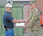 Fred Siebe, Douthit Gunnery Complex Manager, receives a certificate of appreciation from Capt. David Draper, Company C, 299th Brigade Support Battalion, 2nd Armored Brigade Combat Team, 1st Infantry Division.